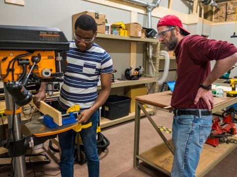 Monty Roper supervises a student with machinery at the maker lab